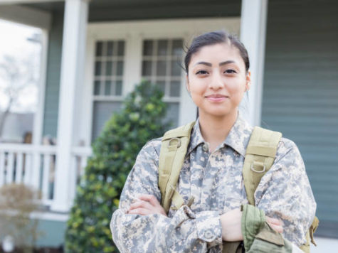 Confident young female soldier is ready for her first overseas deployment. She is standing in front of her home.